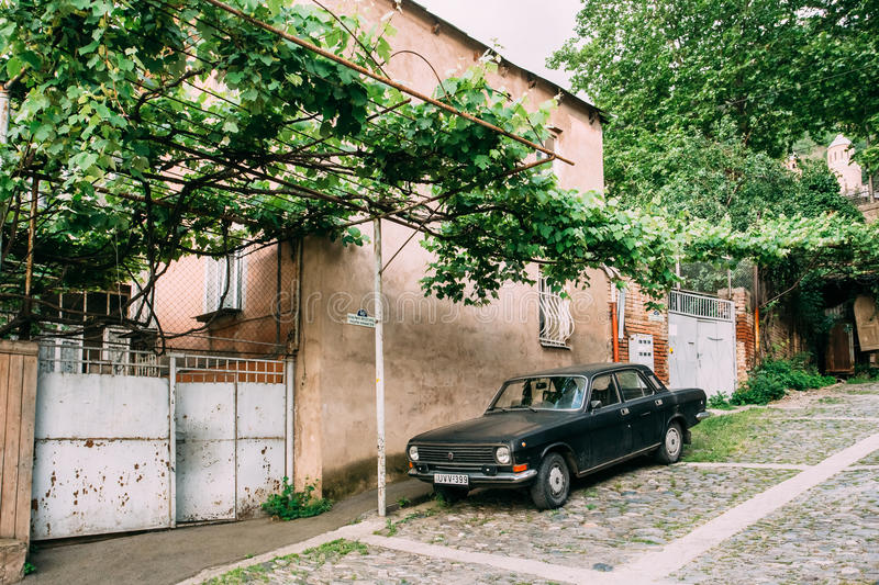 Tbilisi Georgia. Parked Black Volga GAZ Retro Rarity Car Near Private Residential House Under Vine Canopy On Cobbled stock photography