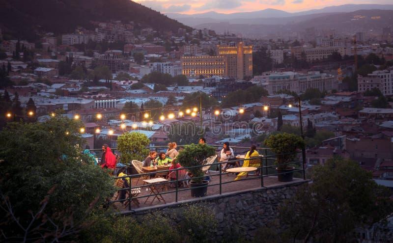 TBILISI GRUZJA, CZERWIEC, - 15, 2017: Ludzie są odpoczynkowi w kawiarni na tarasie w wieczór Restauracja na tarasie chillout zdjęcia royalty free