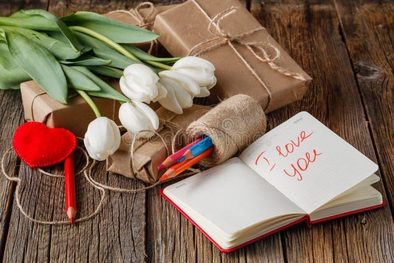 Te amo frase en cuaderno con las flores en la tabla fotografía de archivo