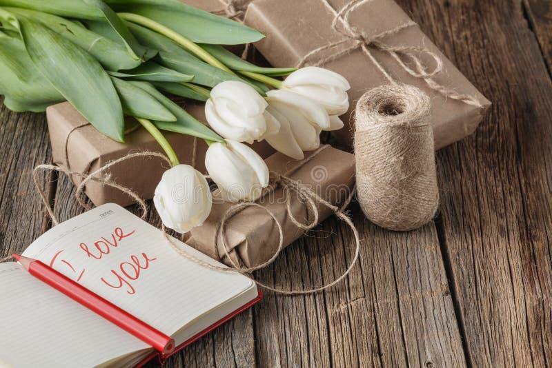 Te amo frase en cuaderno con las flores en la tabla fotografía de archivo libre de regalías