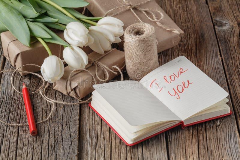 Te amo frase en cuaderno con las flores en la tabla imágenes de archivo libres de regalías
