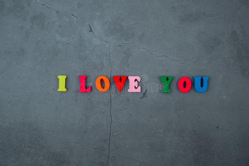 Te amo la palabra multicolora se hace de letras de madera en un fondo enyesado gris de la pared imagen de archivo