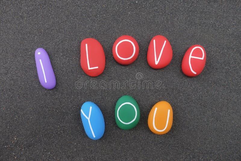 Te amo mensaje con las letras coloreadas multi de las piedras sobre la arena volcánica negra fotografía de archivo libre de regalías
