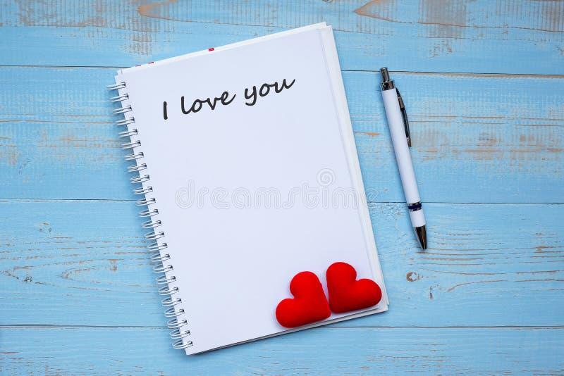 TE AMO palabra en el cuaderno y la pluma con la decoración roja de la forma del corazón de los pares en fondo de madera azul de l imagen de archivo libre de regalías