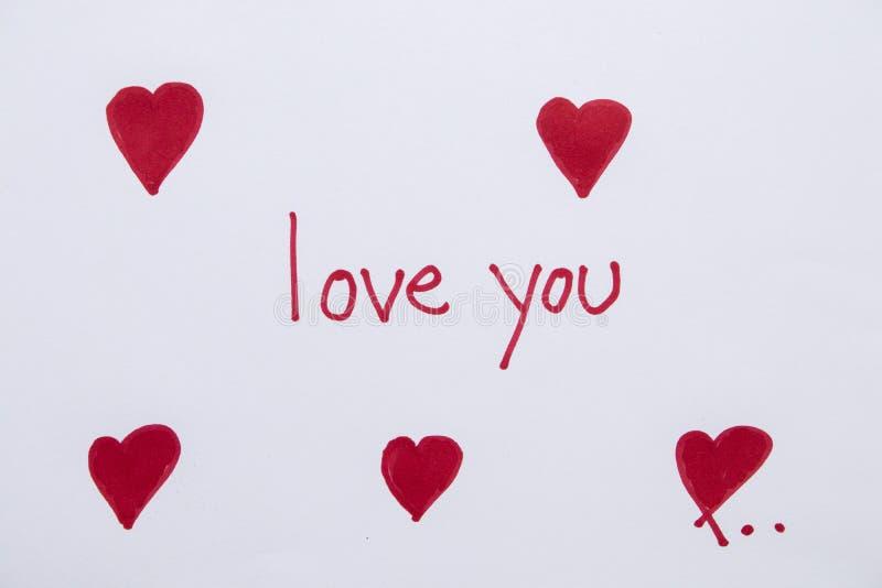 Te amo tarjeta del mensaje con el corazón rojo del drenaje fotos de archivo