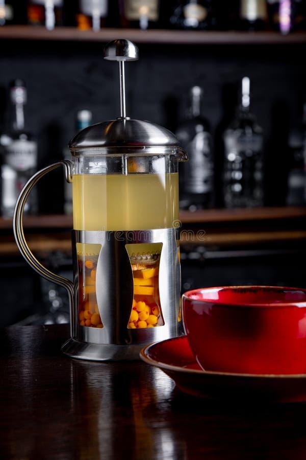 Te för havsbuckthorn i fransk press på en stångbakgrund på coffee shop arkivfoto