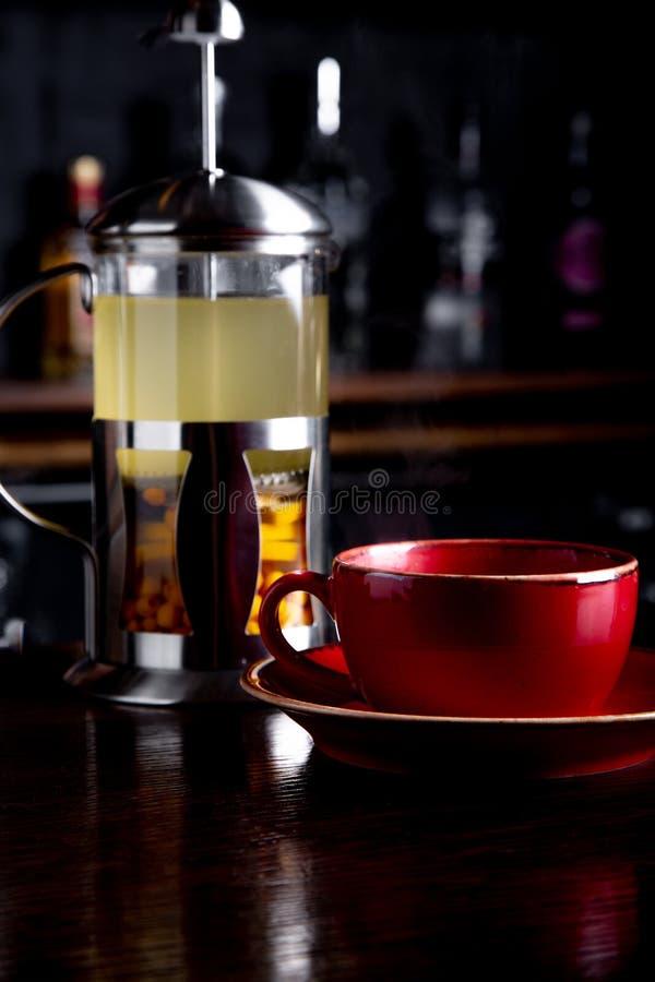 Te för havsbuckthorn i fransk press på en stångbakgrund på coffee shop royaltyfria bilder