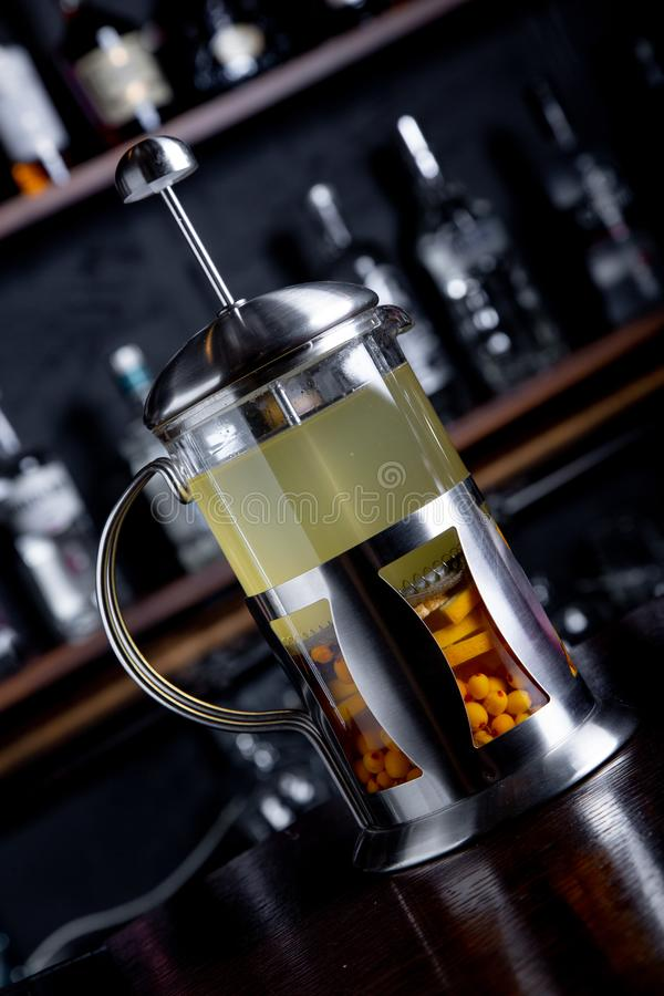 Te för havsbuckthorn i fransk press på en stångbakgrund på coffee shop royaltyfri bild