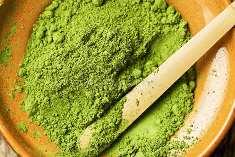 Te för Matcha gräsplanpulver i lerabunke med en traditionell bambusked royaltyfri fotografi