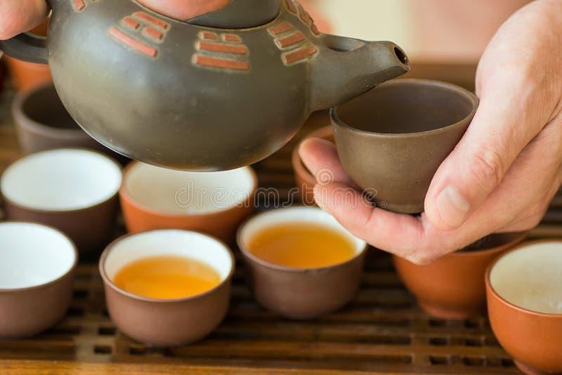 Te för värd för manteförlage hällande in i koppen från krukan på ceremoni Kinesisk japanuppsättning på bambuträmagasinet Nytt bry arkivfoto
