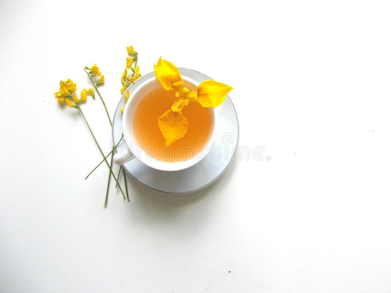 Te i en vit kopp med gula blommor arkivfoto