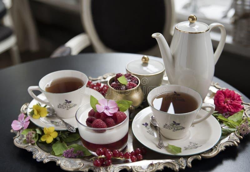 Te i gamla porslinkoppar, panakotaefterrätten och hallonet på ett gammalt försilvrar magasinet retro royaltyfri foto