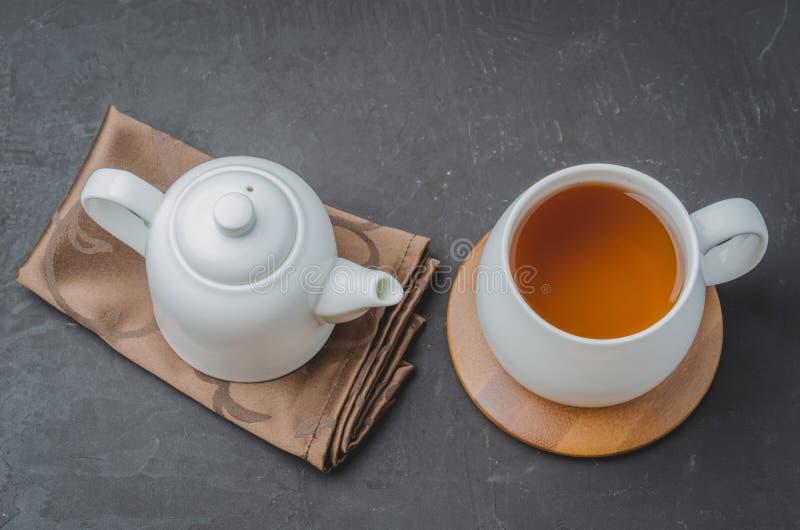Te Kupa av tea och teapoten Vita ware på en svartstentabell Top besk?dar fotografering för bildbyråer