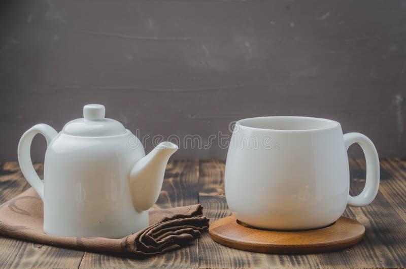 Te Kupa av tea och teapoten Vita ware på en trätabell Selektivt fokusera royaltyfri fotografi