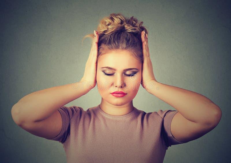 Te luid geluid Mooie jonge vrouw die oren behandelen met handen en ogen gesloten houden royalty-vrije stock foto
