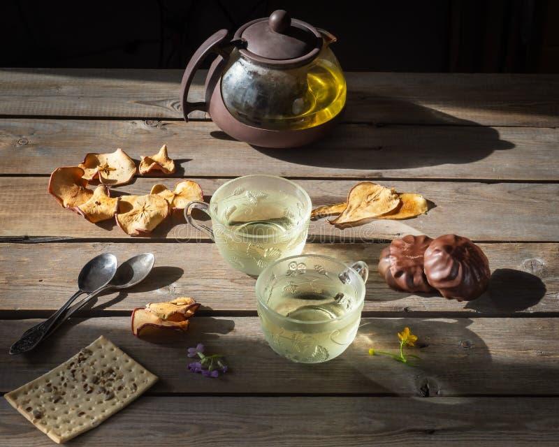 Te med chokladmarshmallower, kex med sädesslag och frö, såväl som fruktchiper, en kokkärl och en kopp av gräsplan arkivfoton