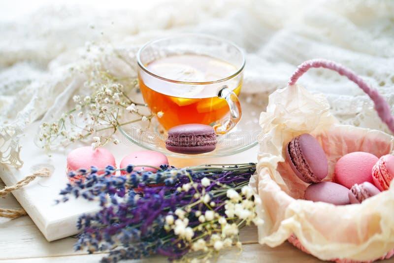 Te med citronen, lösa blommor och macaron på den vita trätabellen arkivbilder