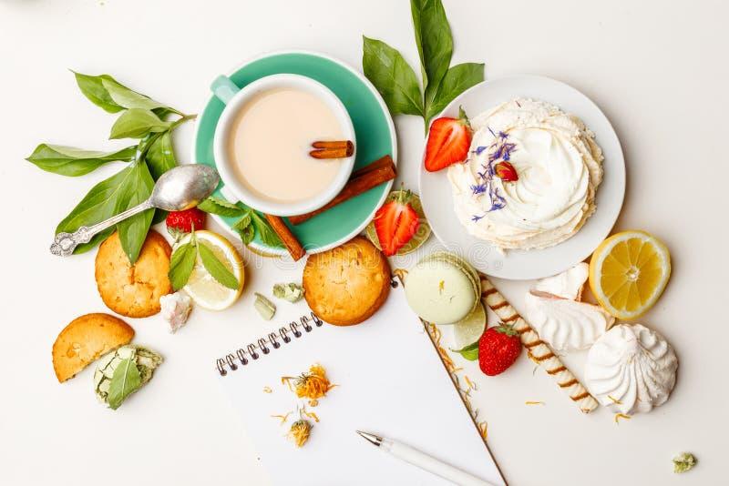 Te med mjölkar på tabellen med sötsaker, jordgubbar och citroner royaltyfria foton
