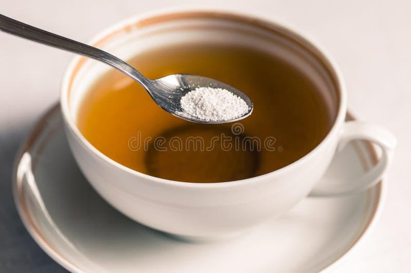 Te med sötningsmedlet i en sked fotografering för bildbyråer