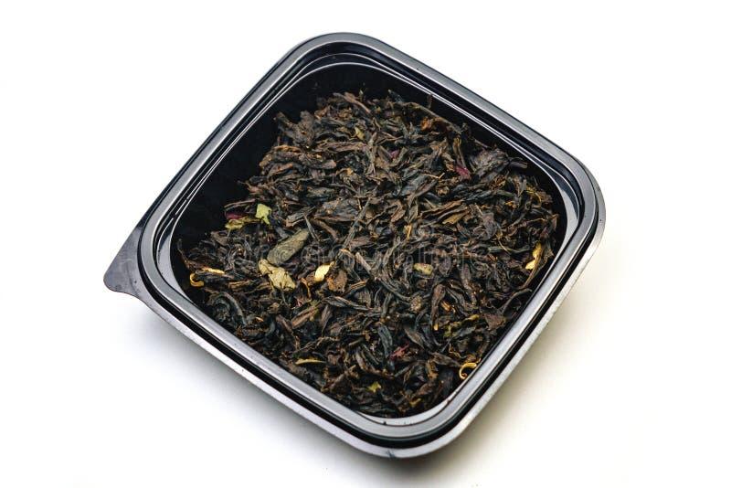 te med torra blommor och med skanning på en svart platta. bakgrund isolerad white. close upp arkivbild