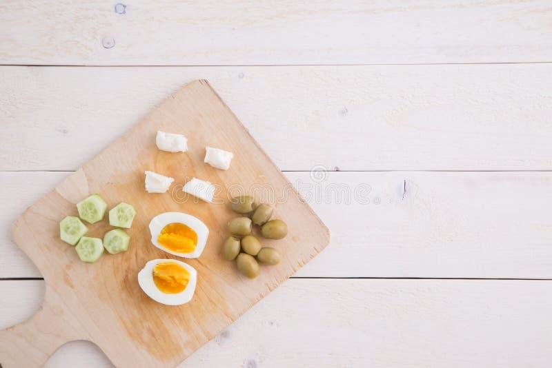 Te och turkisk medelhavs- frukost av oliv, ägg, ost, tomater och gurkor på ett ljust trämagasin på ett vitt naturligt royaltyfri bild