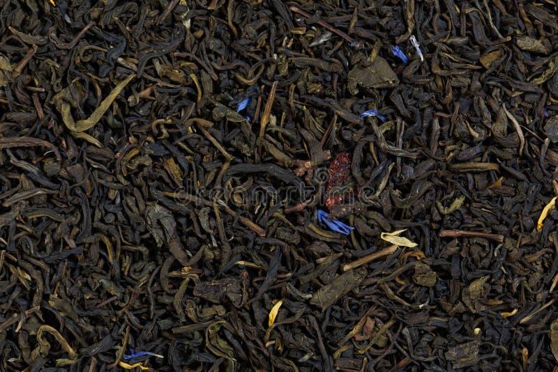 Te på basen av arkCeylon te med den kanderade mango, strawbe arkivfoton