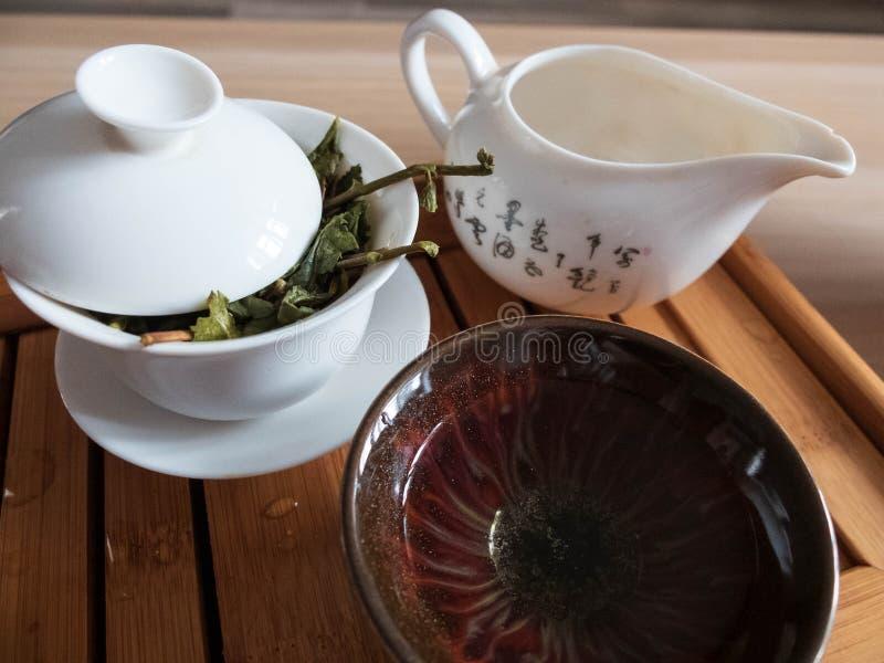 Te som bryggar skyttlar med sidor av oolongte på te som tömmer magasinet Kinesisk traditionell teceremoni royaltyfri bild