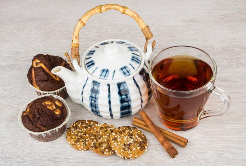 Te, tekanna, kakor, muffin och kanelbruna pinnar på tabellen fotografering för bildbyråer