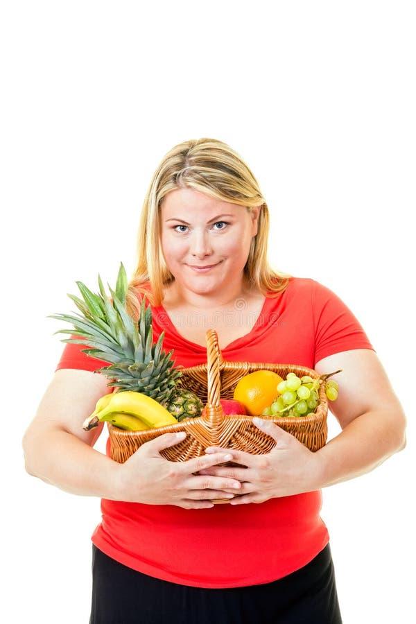 Te zware jonge vrouw met mand vers fruit stock foto's