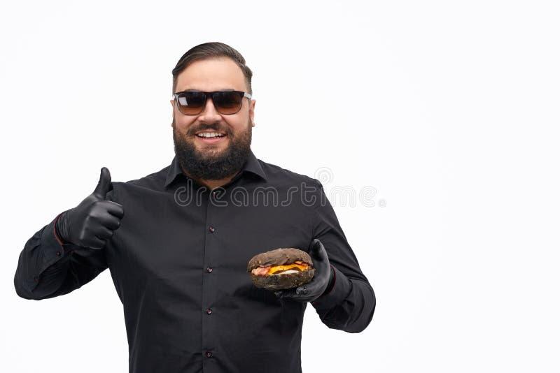 Te zware kerel die hamburger goedkeuren stock fotografie