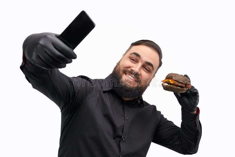 Te zware kerel die selfie met hamburger nemen stock afbeelding
