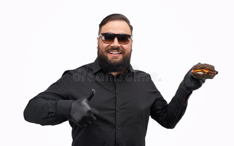 Te zware mens die hamburger tonen en duim gesturing royalty-vrije stock afbeelding