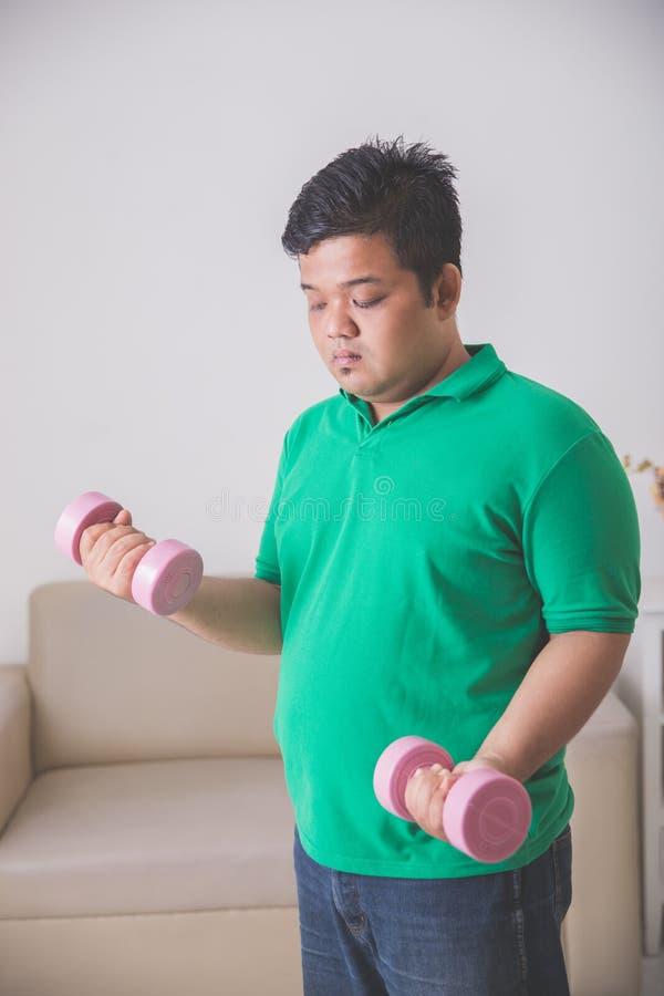 Te zware mens die oefening doen die thuis, een domoor opheffen bij stock foto