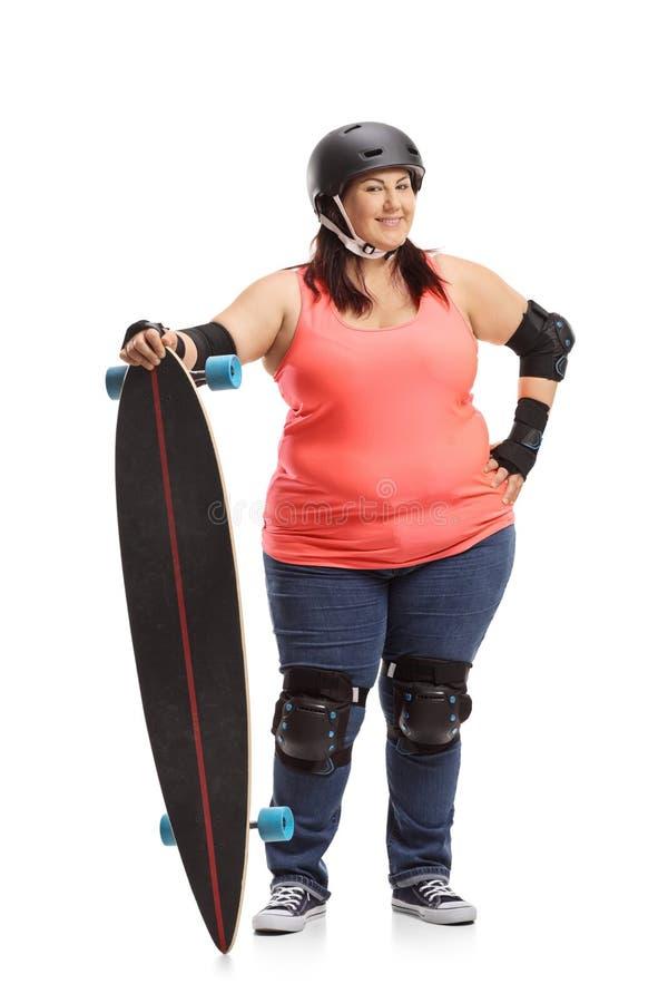 Te zware vrouw die beschermend toestel dragen en een longboard houden stock foto's