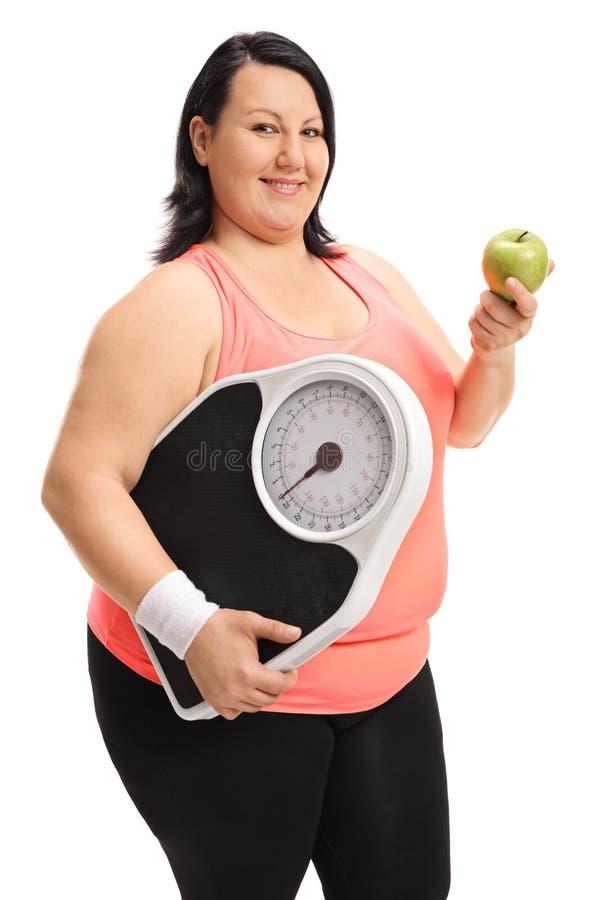 Te zware vrouw die een gewichtsschaal en een appel houden stock foto