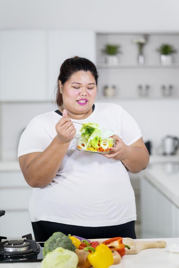 Te zware vrouw die gezonde salade in keuken eten royalty-vrije stock afbeelding