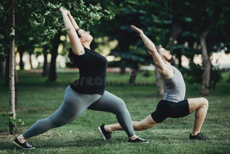 Te zware vrouw die met persoonlijke trainer uitwerken stock foto's