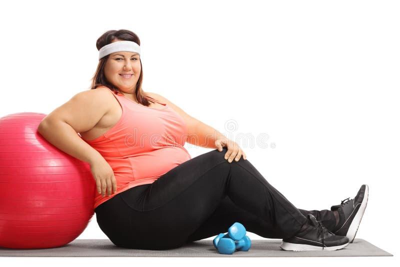 Te zware vrouw die op een pilatesbal leunen stock afbeeldingen