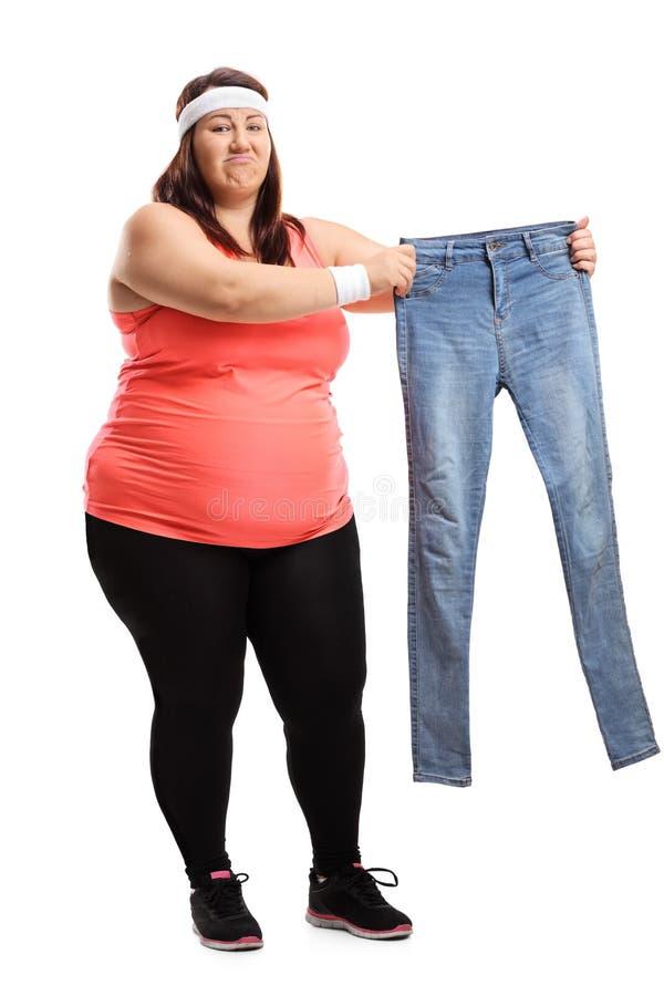 Te zware vrouw die in sportkleding een paar kleine jeans ISO houden royalty-vrije stock fotografie