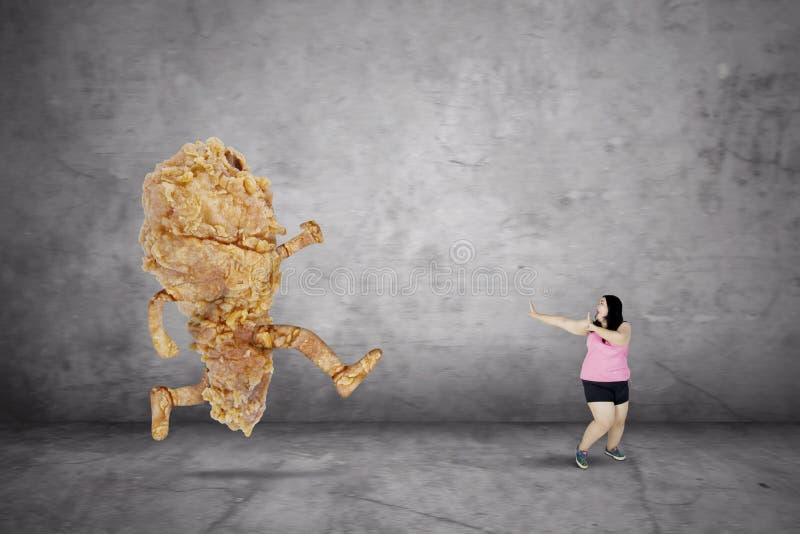 Te zware vrouw die van een gebraden kip ontsnappen stock foto