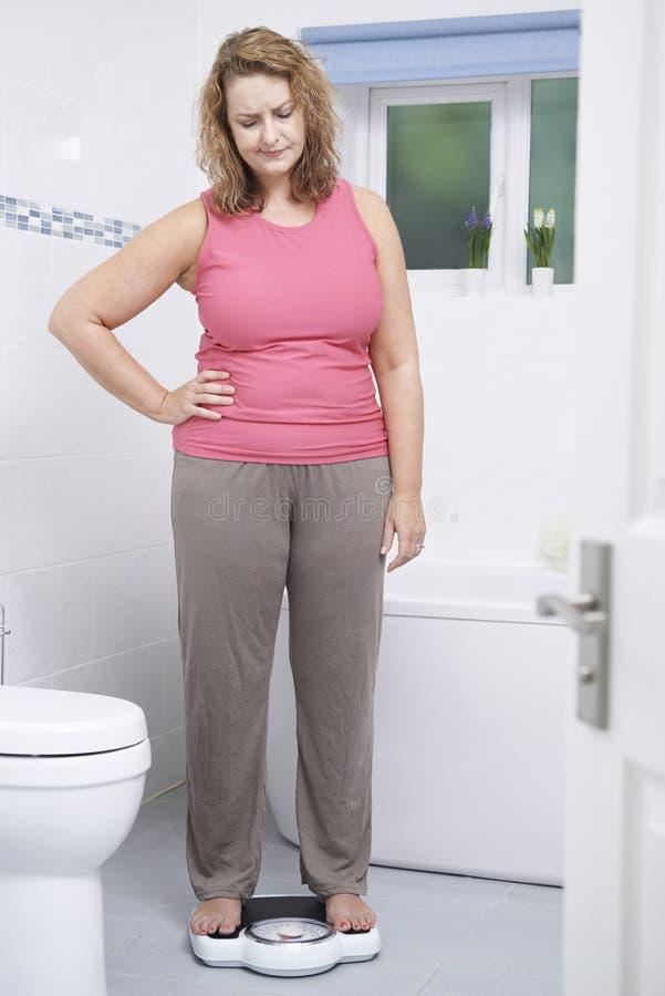 Te zware Vrouw die wegen op Schalen in Badkamers royalty-vrije stock afbeeldingen