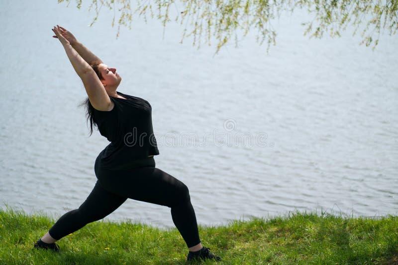 Te zware vrouw die yoga doen, die dichtbij meer ontspannen royalty-vrije stock afbeelding