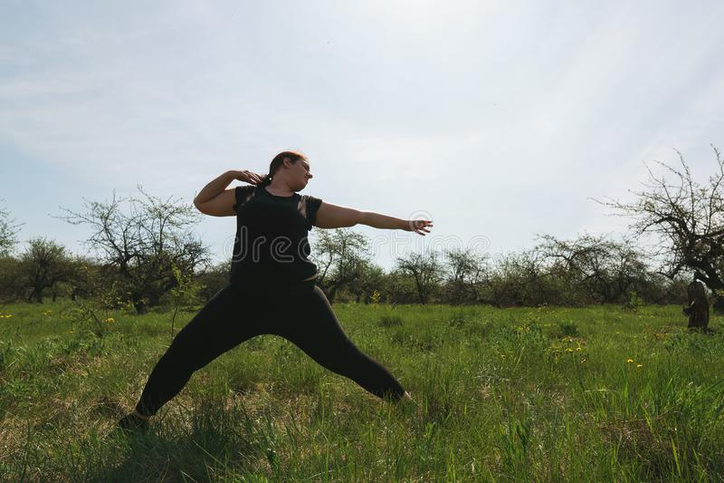 Te zware vrouw die yoga in ochtendpark doen stock foto's