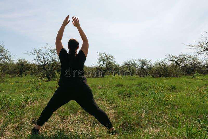 Te zware vrouw die yoga in ochtendpark doen stock foto