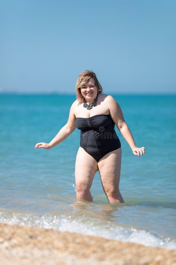 Te zware vrouw in zwart zwempak uit één stuk bij het overzees royalty-vrije stock afbeelding