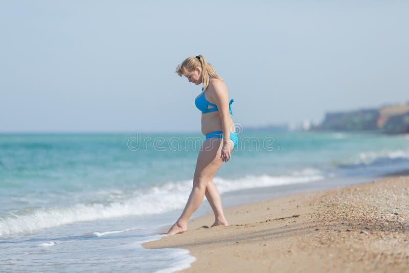 Te zware vrouw in zwempak die in overzees binnengaan stock afbeeldingen