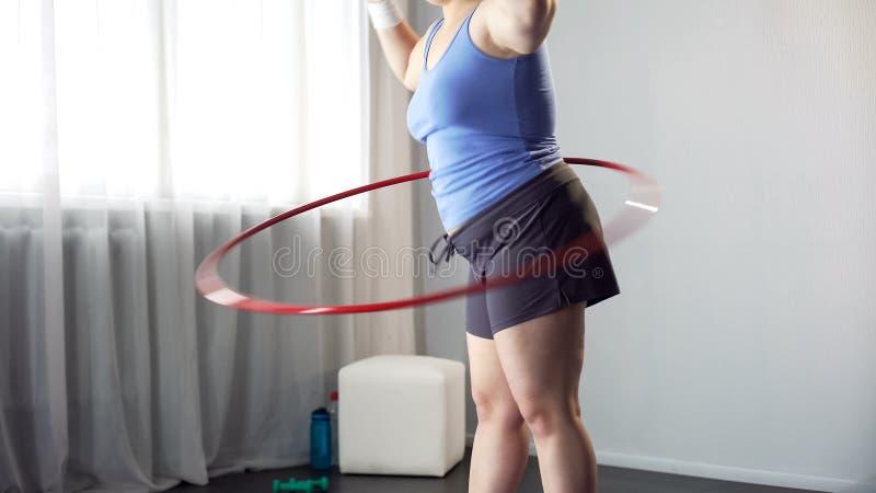 Te zware vrouwelijke tollende hulahoepel, oefening voor gewichtsverlies, vermageringsdieetproces stock foto