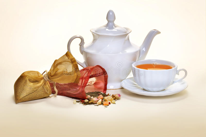 Tea. Pouches with tea for tea leaves and a white teacup and a teakettle with a saucer stock photos