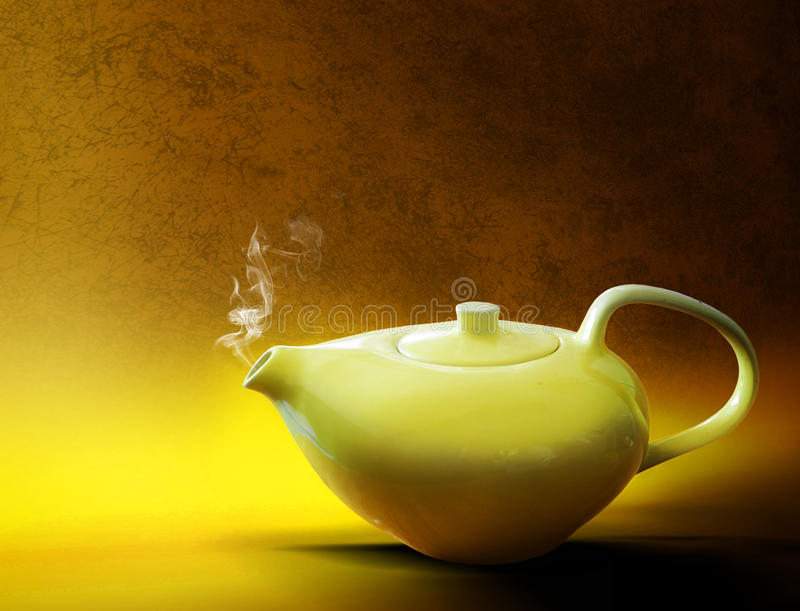 Tea. A steaming yellow ceramic tea pot on a yellow and gold textured background