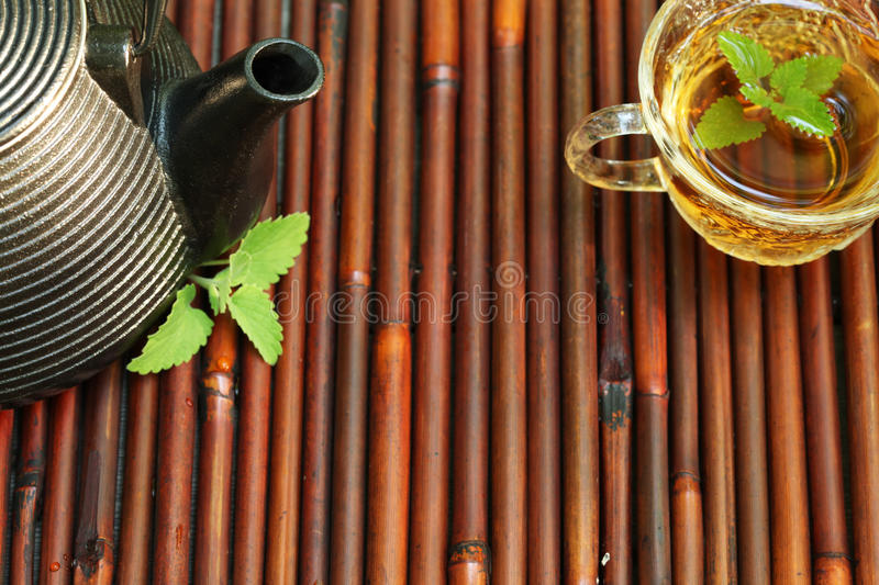 cups with herbal tea and pieces of lemon dried herbs and